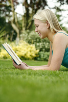 Teenage girl lying forward on the field holding book