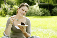 Teenage girl sitting on the field enjoying a piece of cake