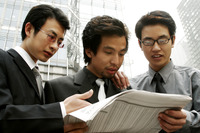 Three businessmen sharing a newspaper