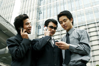 Three businessmen using hand phones