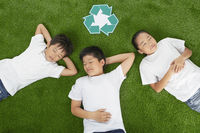 Three children lying on the grass with eyes closed