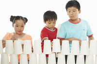 Three children stacking up disposable cups together