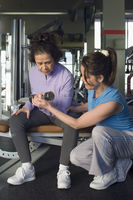 Trainer assisting senior woman in weightlifting with dumbbell