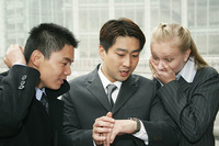 Two asian guys and a lady looking at the time in shock