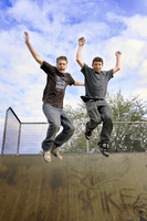 Two boys jumping in a skateboard park