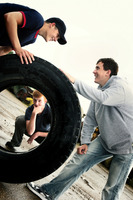 Two boys rolling a big tyre