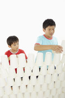 Two boys stacking up disposable cups together
