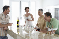 Two couples drinking wine in kitchen