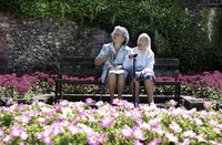 Two old women sitting on a bench in the garden