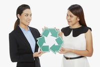 Two women holding up a recycle logo