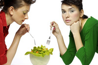 Two women sharing a bowl of salad
