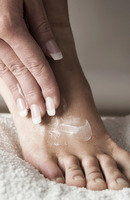 Woman applying lotion on her foot