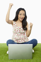 Woman cheering while using laptop