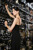 Woman choosing wine in the wine cellar