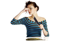 Woman closing her nose while cutting a fish