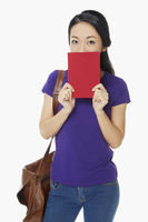 Woman covering her mouth with a book
