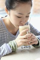 Woman drinking latte in tall glass mug