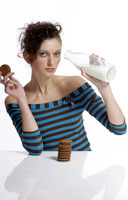 Woman drinking milk while holding biscuit