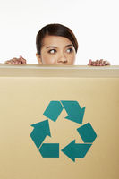 Woman hiding behind a recyclable cardboard box
