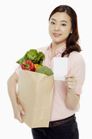 Woman holding a bag of groceries and a shopping list