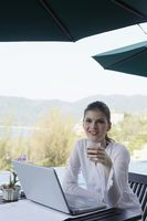 Woman holding a glass of tea and sitting in front of a laptop