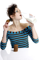 Woman holding biscuit while drinking a bottle of milk