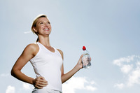 Woman holding bottled water while jogging