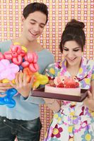 Woman holding cake while man holding sculpted balloons