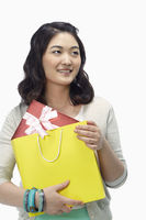 Woman holding on to a paper bag with a gift box in it