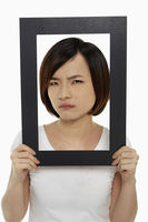Woman holding up a black picture frame, looking angry