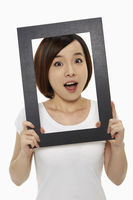 Woman holding up a black picture frame, looking surprised