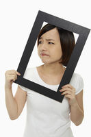 Woman holding up a black picture frame, making a face
