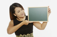 Woman holding up a blank blackboard