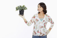 Woman holding up a potted plant