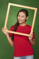 Woman holding up a wooden frame