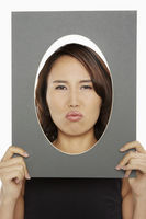 Woman holding up an oval frame