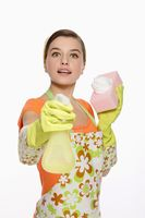 Woman in apron holding spray bottle and cleaning sponge