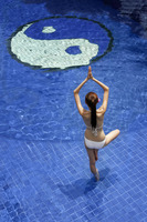 Woman in bikini practicing yoga in the pool