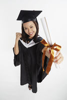 Woman in graduation gown cheering