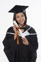 Woman in graduation gown holding a scroll