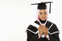 Woman in graduation robe, praying