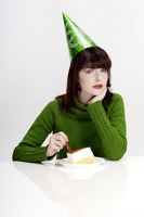 Woman in party hat eating cake