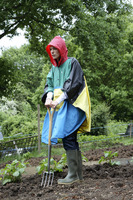 Woman in raincoat holding a spading fork in community garden