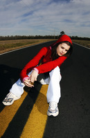 Woman in red hooded jacket sitting in the middle of the road