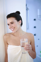 Woman in towel holding a glass of water