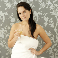 Woman in towel holding a glass of wine