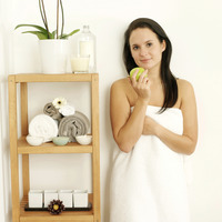 Woman in towel holding a green apple