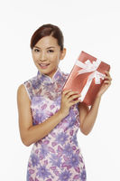 Woman in traditional clothing holding a red gift box