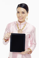 Woman in traditional clothing holding up a digital tablet