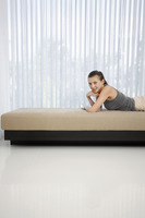 Woman lying forward on sofa